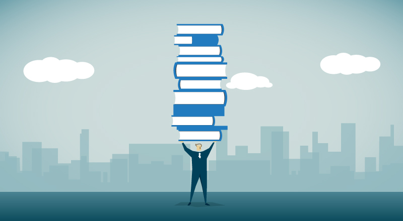 Businessman holding a stack of books above his head.