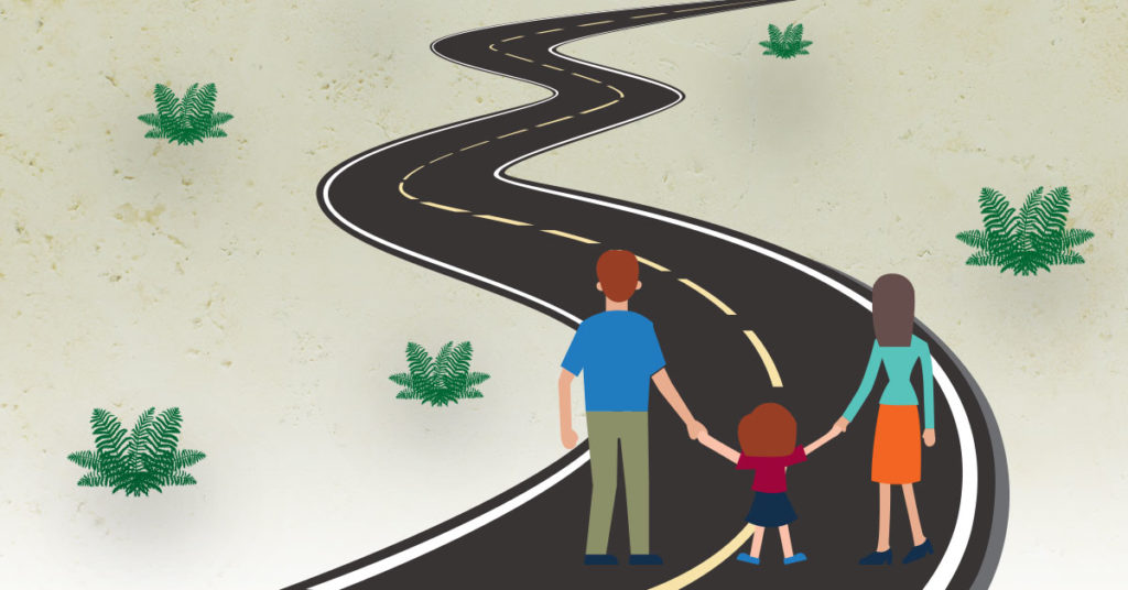 parents holding child's hand standing in the middle of the road